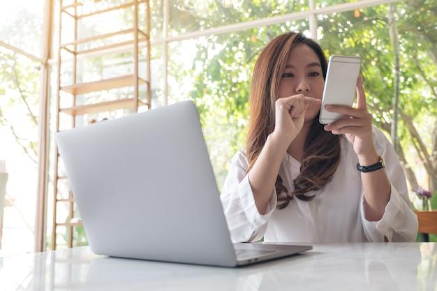 Una bella donna asiatica azienda, alla ricerca e l'utilizzo di smart phone durante l'utilizzo di laptop nella caffetteria
