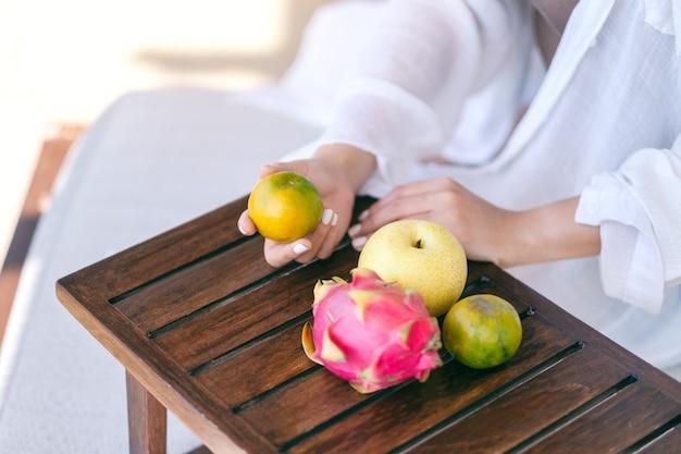 Una bella donna asiatica che tiene un'arancia con la pera e la frutta del drago su un piccolo tavolo di legno