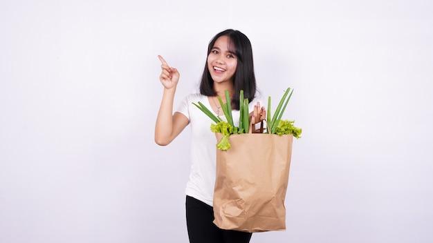 Bella donna asiatica che tiene il sacchetto di carta delle verdure fresche molto felice che indica con la mano e il dito sulla superficie bianca isolata