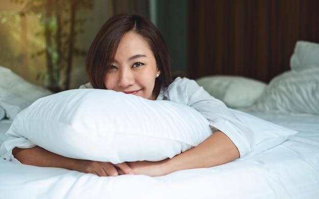 Una bella donna asiatica in possesso di un cuscino mentre sdraiato su un letto accogliente bianco a casa