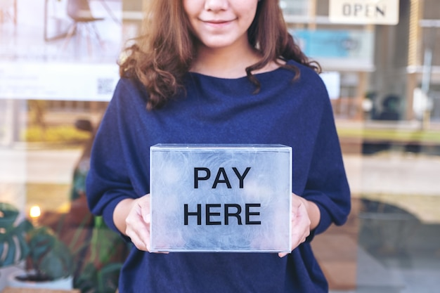 Una bella donna asiatica che tiene una scatola di pagamento di plastica
