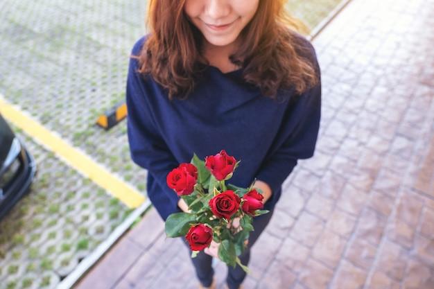 Una bella donna asiatica che tiene le rose rosse fiorisce con la sensazione felice il giorno di san valentino