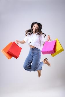 Bella donna asiatica tenendo le borse della spesa di vari colori e saltando con una felice espressione su uno sfondo bianco.