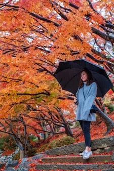 Bella donna asiatica che tiene un ombrello mentre levandosi in piedi fra le foglie dell'albero di colori rosso e giallo in autunno
