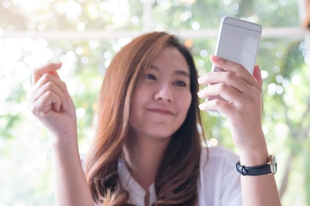 Una bella donna asiatica holding, utilizzando e guardando smart phone con sentirsi felice