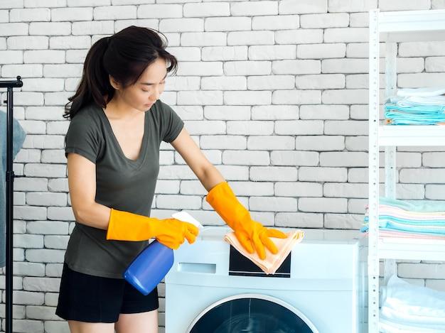 Bella donna asiatica, casalinga che indossa guanti di gomma protettivi arancioni utilizzando spray detergente e panno pulito per la pulizia della lavatrice sul muro di mattoni bianchi