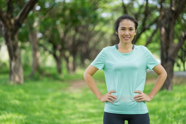 La bella donna asiatica sta esercitandosi nel parco.