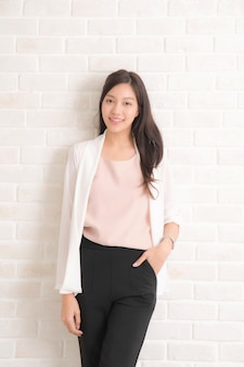 Capelli castani lunghi della bella donna asiatica che sorridono e che affrontano la sua vista laterale con indossare una maglietta nera e jeans in piedi positng sulla parete di colore beige.