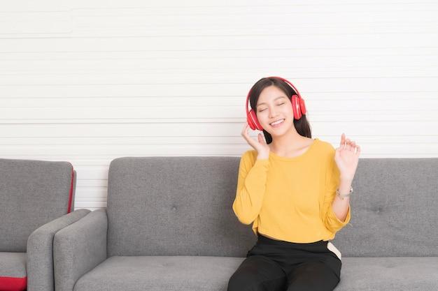 Capelli lunghi della bella donna asiatica che indossa una camicia gialla con le cuffie rosse che si rilassano sul divano, sta ascoltando la musica, il chill out e il concetto di svago.