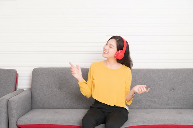 Capelli lunghi della bella donna asiatica che indossa una camicia gialla con le cuffie rosse che si rilassano sul sofà, sta ascoltando la musica