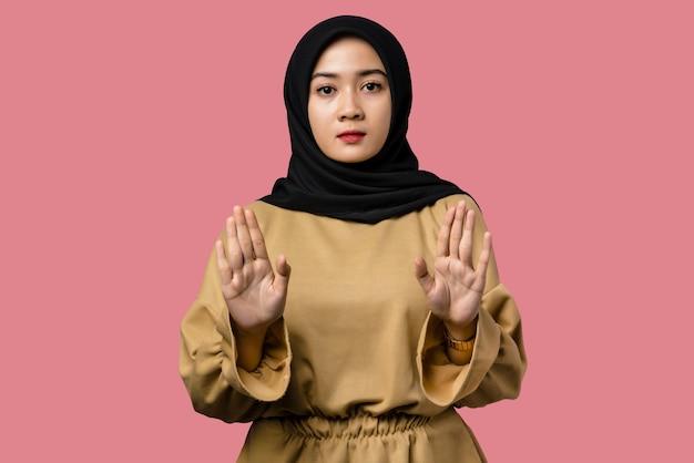 Bella donna asiatica che fa il fanale di arresto con l'espressione di rifiuto della mano