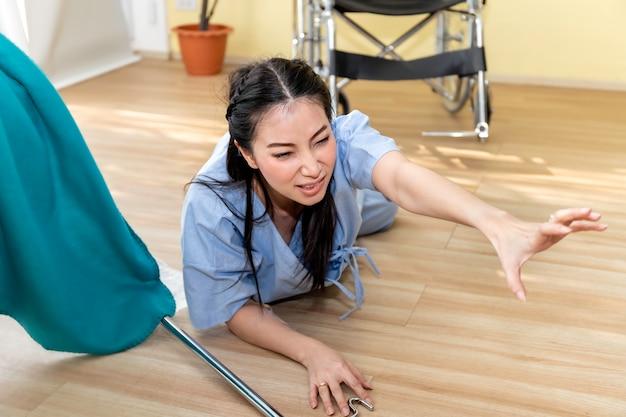 Incidente paziente della bella donna asiatica che cade e che striscia per l'aiuto nella stanza di ospedale.