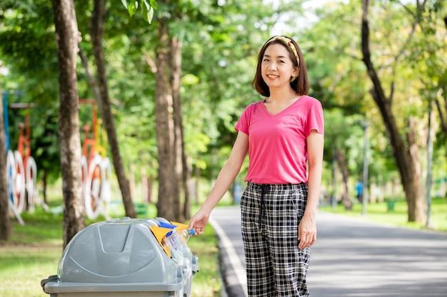 Bella donna asiatica che mette le bottiglie di acqua nel riciclaggio dello scomparto giallo