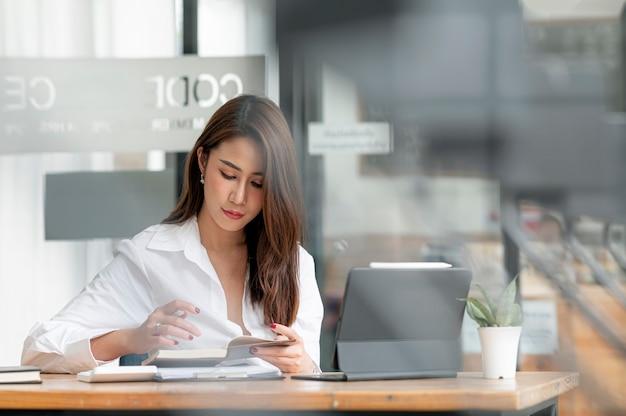 Bella donna asiatica che legge un libro mentre è seduto al tavolo con tablet computer.