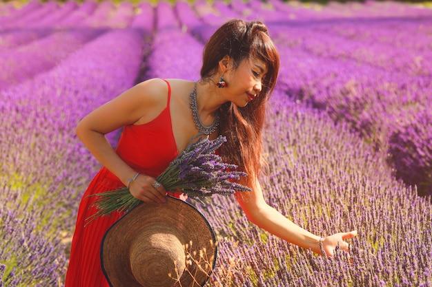 Bella donna asiatica in vestito rosso sul campo di lavanda