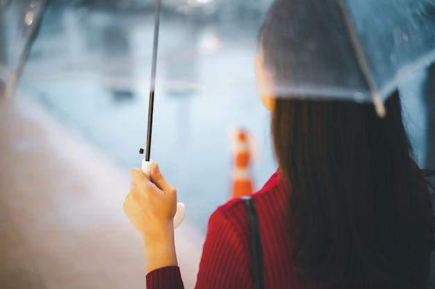 Bella donna asiatica in maglione rosso in piedi accanto alla strada mentre piove e tiene un ombrello