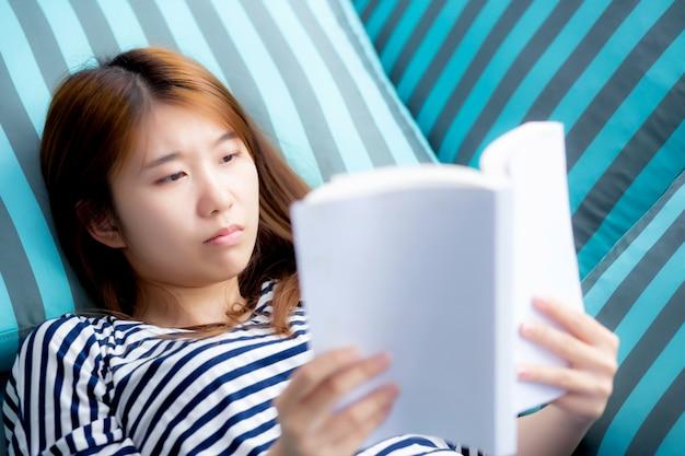 La bella donna asiatica si distende il libro di lettura di menzogne sul sofà
