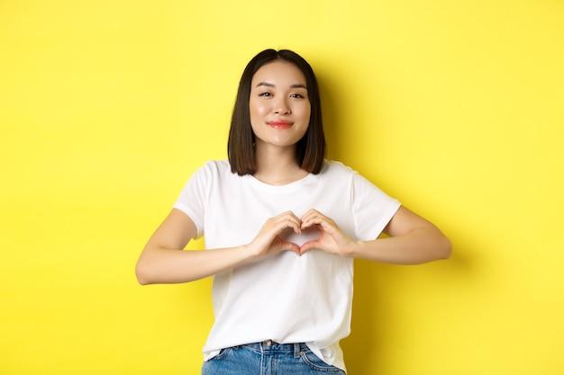 Bella donna asiatica che mostra ti amo gesto di cuore, sorridendo alla telecamera, in piedi su sfondo giallo. concetto di san valentino e romanticismo