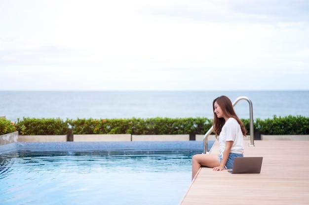 Una bella donna asiatica seduta a bordo piscina con un computer portatile