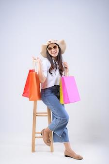 Bella donna asiatica seduta su una sedia in possesso di una borsa della spesa con un volto sorridente su sfondo bianco.