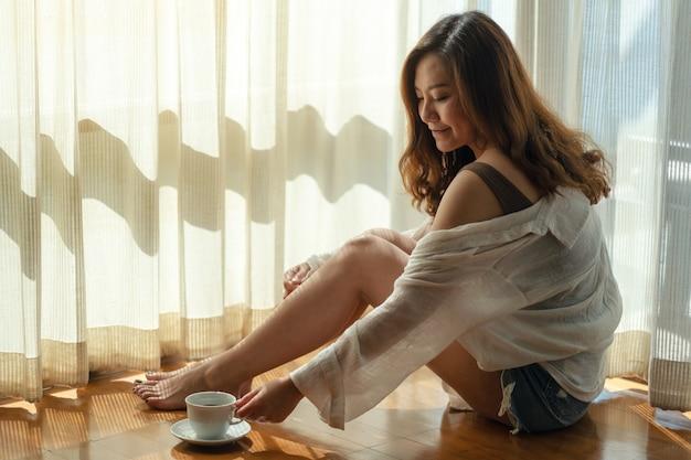 Una bella donna asiatica seduta e afferrando una tazza di caffè caldo da bere sul pavimento al mattino