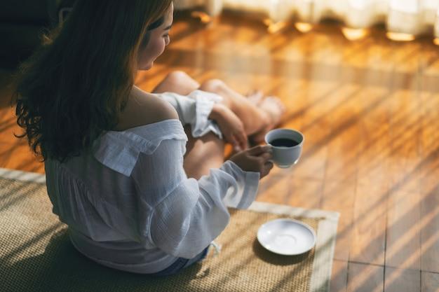 Una bella donna asiatica che si siede e che tiene una tazza di caffè caldo da bere sul pavimento al mattino