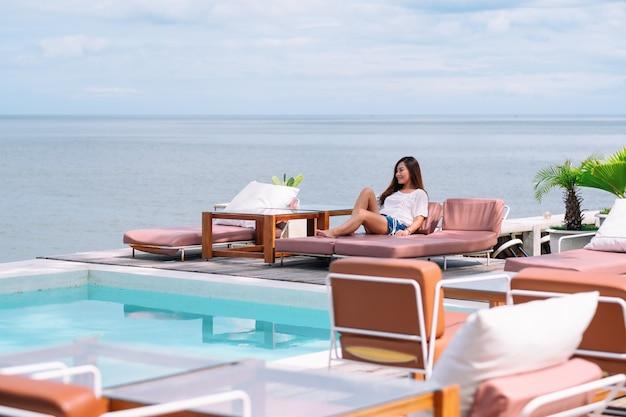 Una bella donna asiatica seduta e sdraiata su un letto a bordo piscina e al mare