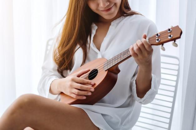 Una bella donna asiatica che si siede e che gioca ukulele in camera da letto