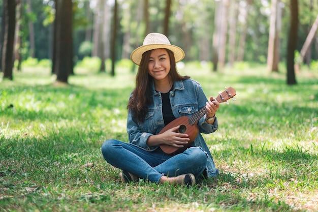 Una bella donna asiatica che si siede e che gioca ukulele nel parco