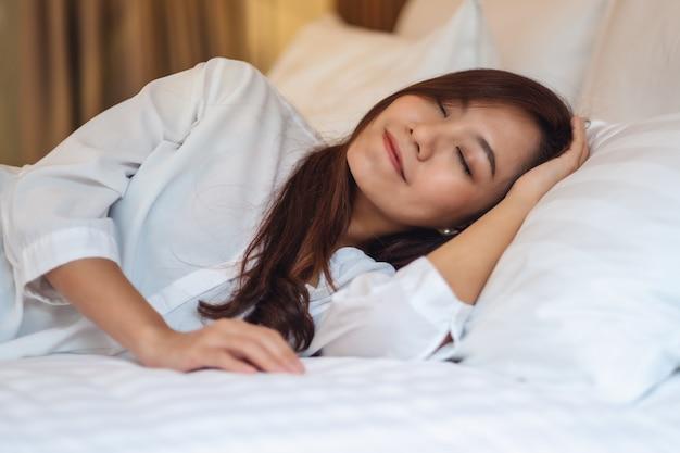 Una bella donna asiatica che dorme in un letto accogliente bianco a casa