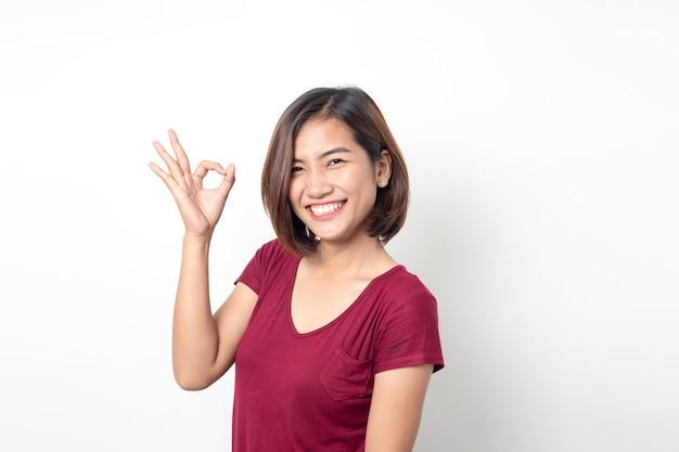 Bella donna asiatica che sorride con il segno giusto della mano su una priorità bassa isolata bianca
