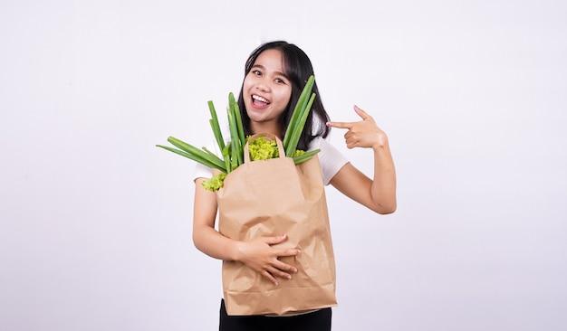Bella donna asiatica sorridente con un sacchetto di carta di verdure fresche con superficie bianca isolata