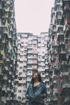 Una bella donna asiatica in piedi tra l'affollato edificio residenziale della comunità di quarry bay, hong kong