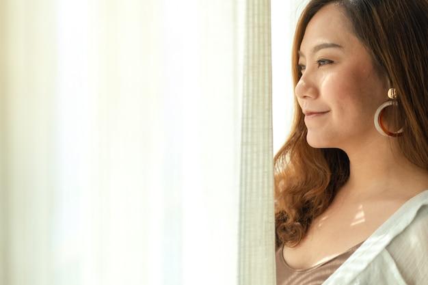 Una bella donna asiatica in piedi accanto alle tende bianche al mattino