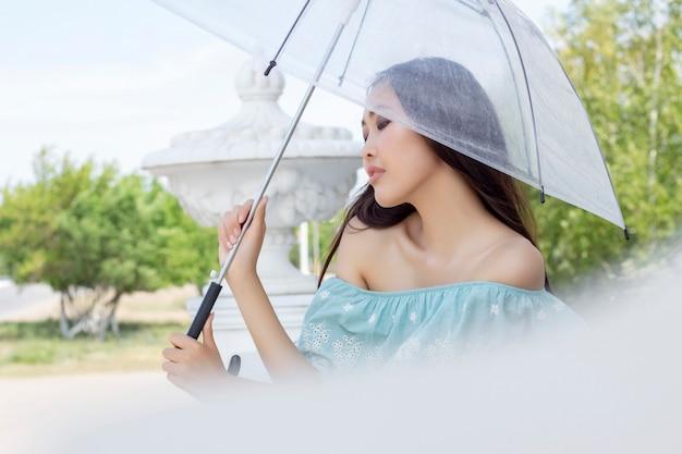 Bella donna asiatica in piedi con l'ombrello trasparente