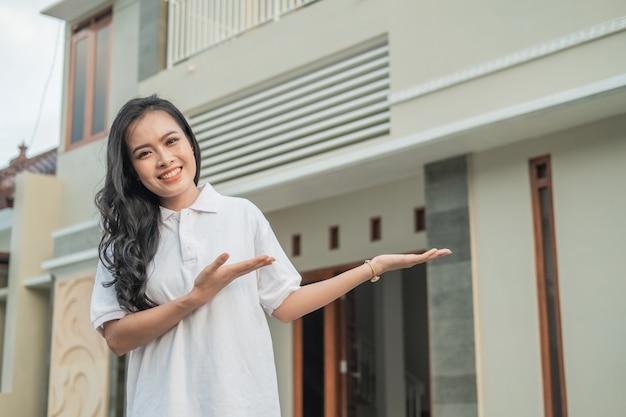 La bella donna asiatica sta con un gesto della mano per offrire qualcosa davanti alla nuova casa