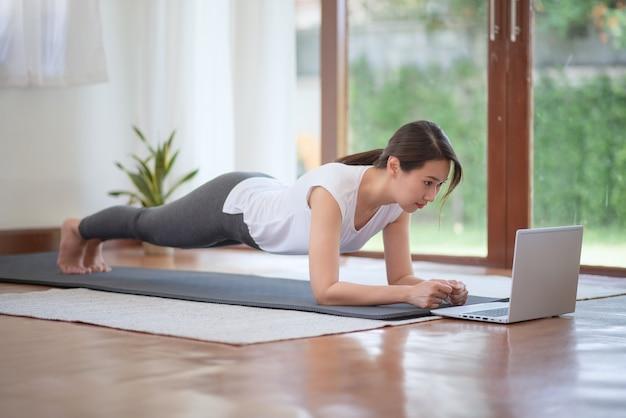 Bella donna asiatica che rimane in forma esercitando a casa per uno stile di vita sano di tendenza