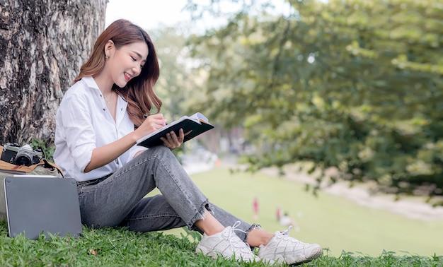 Bella studentessa asiatica seduta sotto il grande albero all'aperto, scrivendo sul taccuino in mano con felicità.