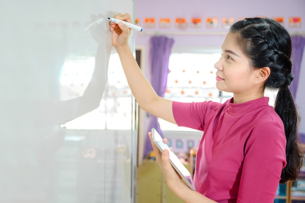 Bella insegnante asiatica che scrive sulla lavagna bianca insegnando agli studenti a scuola in classe per l'istruzione