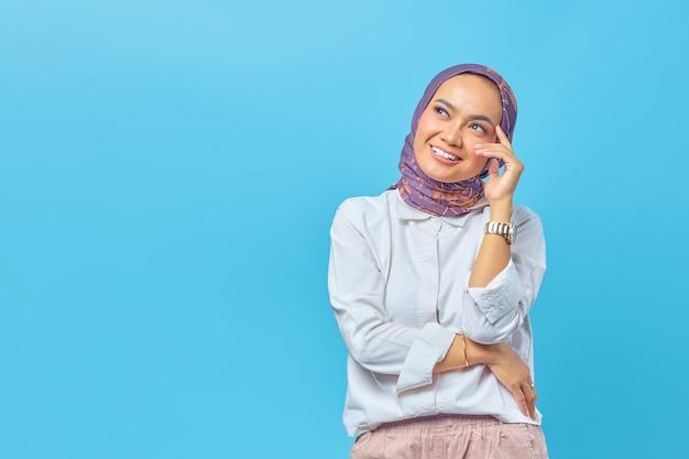 Bella donna asiatica che pensa a un'idea isolata su sfondo blu