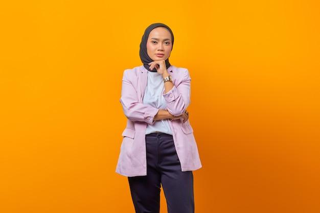 Bella donna asiatica che pensa con la mano sul mento disegnata guardando avanti su sfondo giallo