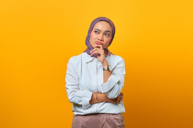 Bella donna asiatica che pensa con la mano sul mento interessata a guardare su sfondo giallo