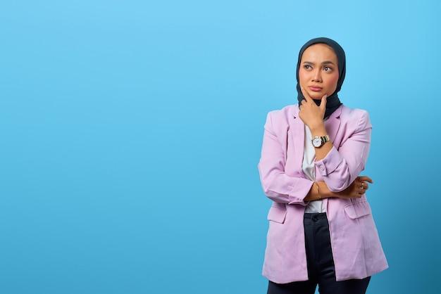 La bella donna asiatica pensa a qualcosa e si tocca il mento su sfondo blu