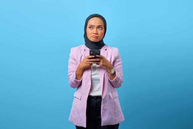 La bella donna asiatica pensa a qualcosa mentre tiene il cellulare su sfondo blu