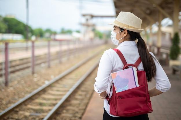 Misure di sicurezza del viaggiatore di bella donna asiatica nella stazione ferroviaria, concetto di viaggio