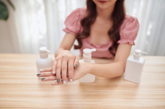 Bella donna asiatica che usa disinfettante per le mani a casa.