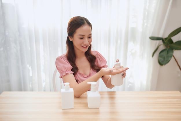Bella donna asiatica che utilizza disinfettante per le mani durante l'introduzione di prodotti.
