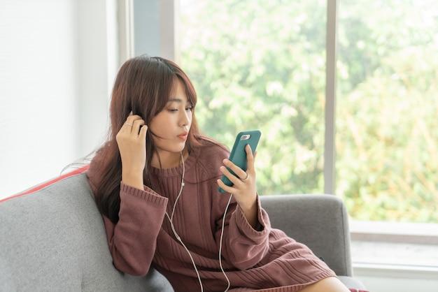 Bella donna asiatica utilizza lo smartphone sul divano grigio nel soggiorno