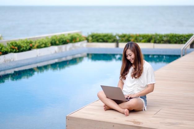 Una bella donna asiatica che usa e digita sul computer portatile mentre è seduta a bordo piscina