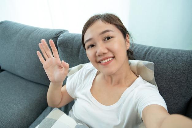 Una bellissima vlogger asiatica muove la mano e sorride alla telecamera mentre fa una videochiamata. giovane donna che si rilassa in soggiorno e alza la mano mentre usa la videochiamata alla sua famiglia.